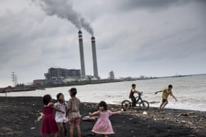 Children play by the beach near a coal power plant in Jepara, Central Java