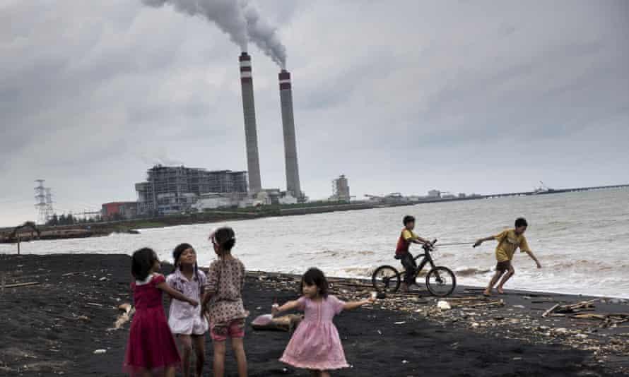 Children play by beach near coal plant