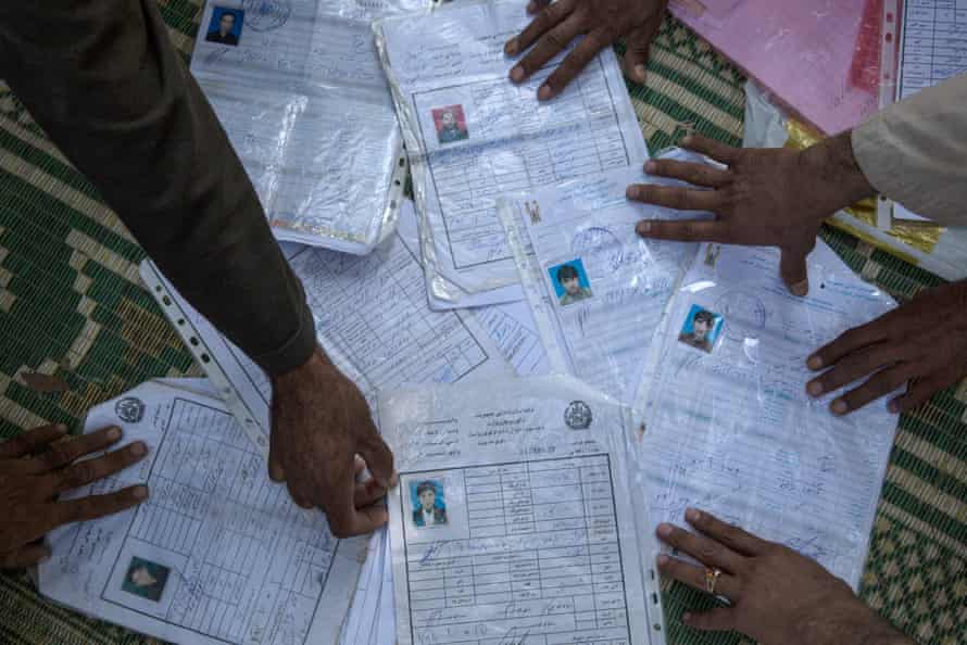 Familes in Javari village, Khogyani, show the 'taskeras' - the identification documents of those who died.