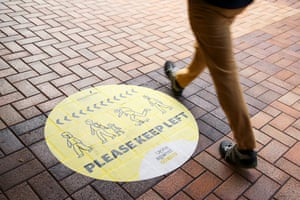 A pedestrian walks past a social distancing sign ahead in Wellington