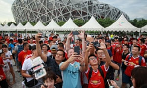 Fans take selfies as they gather near the National Stadium after the match between Manchester United and Manchester City was called off in Beijing