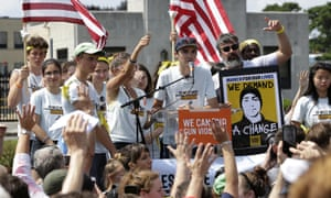 David Hogg, center, a survivor of the school shooting at Marjory Stoneman Douglas high school, in Parkland, Florida, addresses a rally in front of the headquarters of gun manufacturer Smith & Wesson in Springfield, Mass on 26 August.