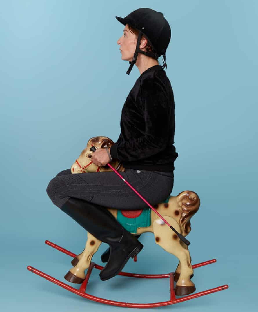 Zoe Williams wearing riding hat and sitting on a rocking horse