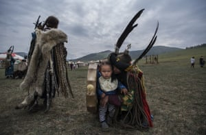 A shaman sits with his child before a fire ritual