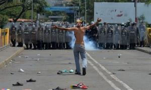A protester in front of Venezuelan national policemen standing guard at the Simon Bolivar international bridge, in Cucuta, Colombia.