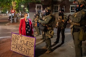 Oregon, US. A protester stands in front of federal officers in Portland.