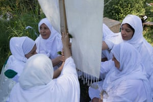 "Women hold a darfash, ""a cross with cloth hanging on it"" used by Mandaeans as a symbol of their religion."