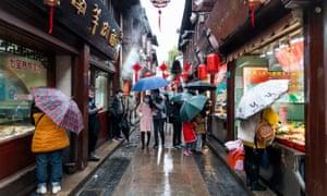 People walk through a street in Shanghai