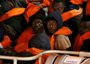 Valletta, Malta: rescued migrants look on from a military vessel as it returns to harbour
