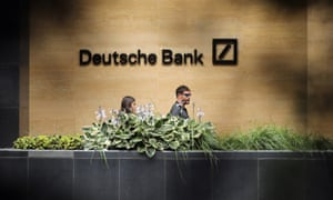 People walk past a Deutsche Bank office in London.