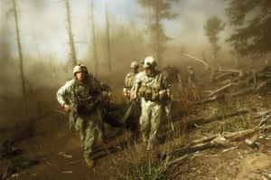 US troops carry the body of a man killed by Taliban insurgents in the Korengal Valley, Afghanistan, October 2007
