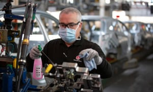 A member of staff at Vauxhall car factory cleaning and disinfecting a work station