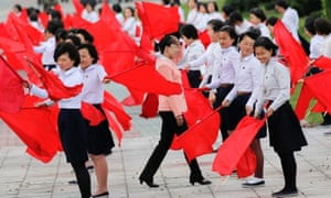 Girls practice dancing with red flags ahead of Friday's celebration.