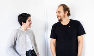 Roberta Gerhard and Marc Vinas standing, looking at each other, hands in pockets, smiling, a white background