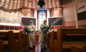 Disinfection workers wearing protective clothing spray anti-septic solution in an Yoido Full Gospel Church in Seoul.