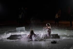 Orthodox believers bathe in icy water shortly after midnight during a traditional Epiphany celebration in a lake near Vilnius.