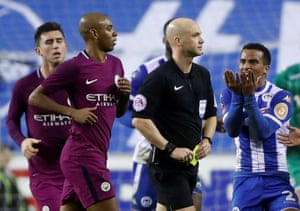 Anthony Taylor holds a yellow card before showing Delph a red.