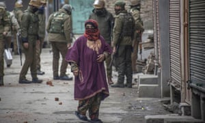 A Kashmiri Muslim woman walks looks on as Indian government forces stand guard
