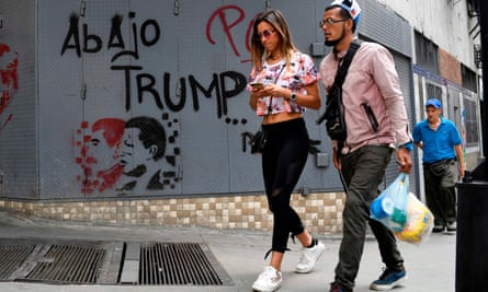 People walk past a wall reading 'Down with Trump' in Caracas, Venezuela