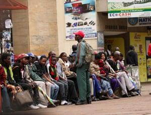 People queue to withdraw money outside a bank in Harare