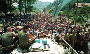 Dutch UN peacekeepers sit on top of an armoured personnel carrier as Muslim refugees from Srebrenica gather in the nearby village of Potocari in July 1995.