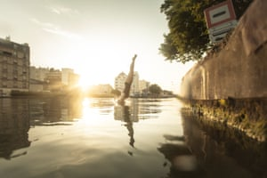 Silhouetted by the sunset a swimmer dives headlong into a canal in east Paris. It's sort of a 'citizen act' to go and swim in Paris. Different mayors of Paris have been saying for years that people would be able to swim in the Seine. Our new mayor wants the river to be used for open-water swimming in the 2024 Olympics. We just want to show that it is possible!
