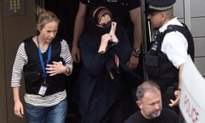 Oficerët e policisë shoqërojë një grua në një furgon policie, pas bastisjen një bllok të banesave në Barking
