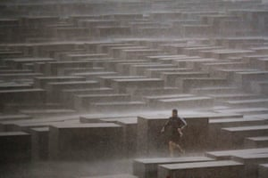 Berlin, GermanyA man runs for cover through the city's Holocaust memorial during heavy rain.