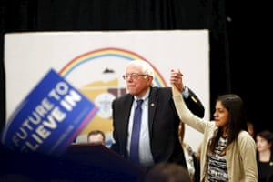 Bernie Sanders holds up the hand of immigrant youth leader Katherine Bueno during a town hall event at the Navajo Nation casino in Flagstaff, Arizona.