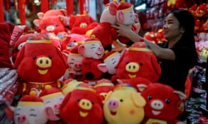 A woman looks at soft toys marking the Year of the Pig in a stall in the Chinatown district of Singapore.