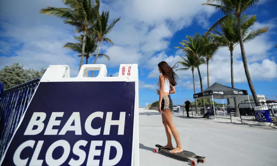 A skateboarder passes a 'Beach Closed' sign on the boardwalk in Miami Beach, Florida, on 20 March. Some Republican mayors in the state had kept beaches open during spring break.