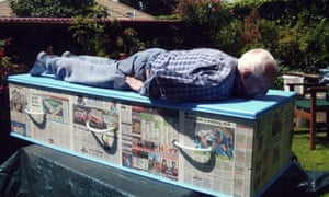 Colin Barnett, a member of the Kiwi Coffin Club, planking on his wallpapered, newspaper coffin.