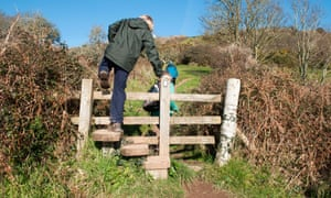 A walker climbing over a wooden stile on the South West Coastal Path.