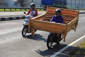 Surakarta, Indonesia A street vendor riding a motorcycle carries a wooden bed, trying to find costumers