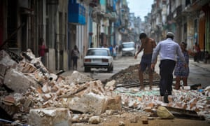 Cubans wade through the rubble from a collapsed building in Havana. Many of the city's historic structures have received little maintenance in over the years.