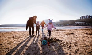 Senior couple enjoying playing with their grandchildren on the beach. Its cold outside so they are wrapped up warm.