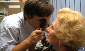 A GP checks a patient's eyes