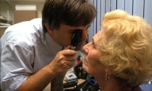 Male GP checking female patients eyes.