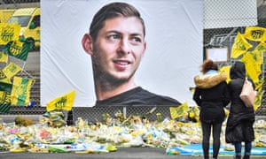 People look at tributes in front of a portrait of Emiliano Sala at the Beaujoire stadium in Nantes in February.