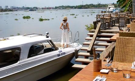 Boat tied up at riverside bar, Vietnam