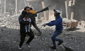 A Syrian man carries an baby injured by the government attack in eastern Ghouta