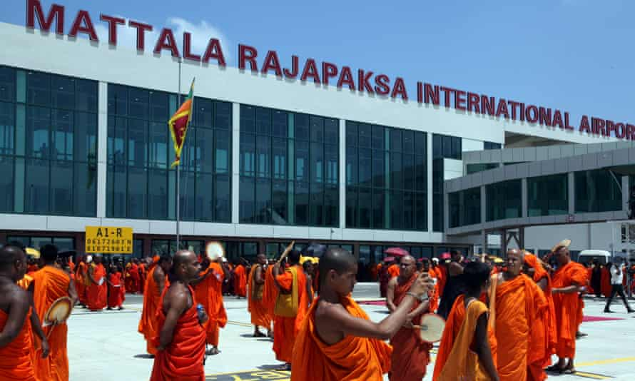 Sri Lankan monks take pictures at the opening of an airport built with Chinese money in Hambantota