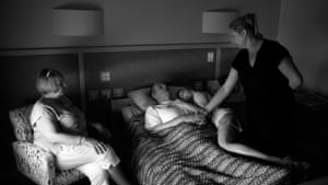 An elderly man lying on a bed with family around him