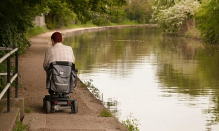 Disabled man using disability scooter on towpath in Warwickshire