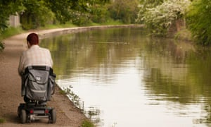 A man using a disability scooter on the towpath of the Grand Union canal at Warwick,.