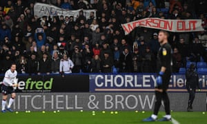 Andrew Taylor of Bolton removes tennis balls thrown on to the pitch amid a protest against the chairman, Ken Anderson, before January's game with West Brom