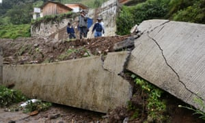 Residents survey the damage from a mudslide following heavy showers caused by the passing of tropical storm Earl in the town of Temazolapa, in Veracruz state, Mexico.