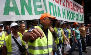 Sanitation workers shout slogans as they protest to oppose job lay-offs, in front of the Greek Parliament in Athens, on 29 June.