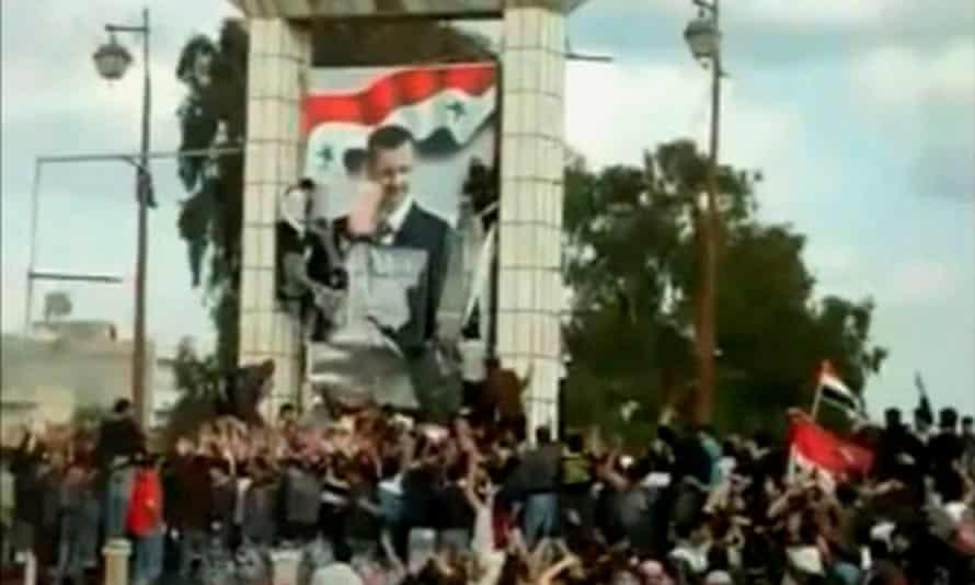crowd around a huge poster of Assad