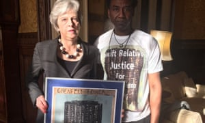 Theresa May holds a painting by the artist Damel Carayol, who lost his niece in the Grenfell Tower fire.